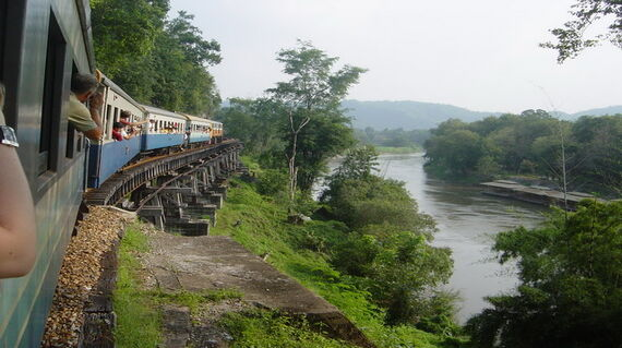 Train passing beside river Kwai in Thailand